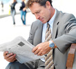Business man reading newspaper outside