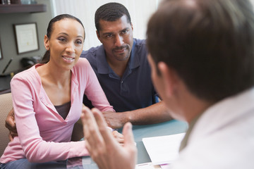 Couple having discussion with doctor in IVF clinic