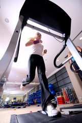 Girl running on the treadmill in the gym