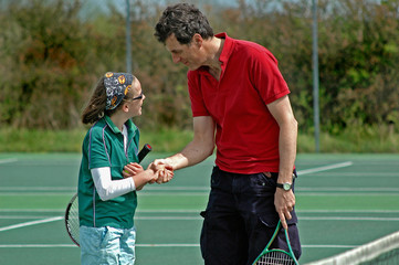 father and daughter shaking hands after tennis match