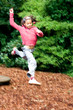 Young girl having fun leaping high from a wooden board,