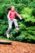 Little girl leaps in the air, jumping off a wooden board