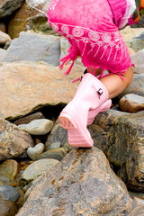 Young girl carefully placing her feet on slippery rocks