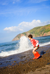 Young boy trying to escape the rolling waves