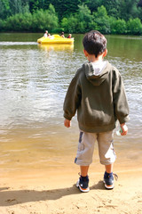 Young boy standing by the side of the lake