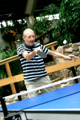 Active senior gentleman playing indoor table tennis.