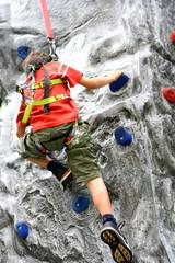 Young boy enjoying the indoor rock climbing,
