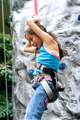 Young girl climbing down from rockclimbing activity