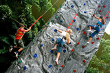 Young children doing rock climbing in an indoor sports center.
