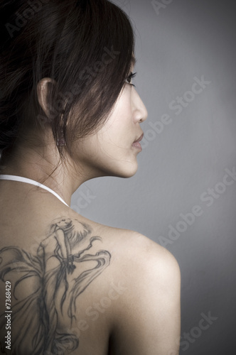 rear view of adult woman with tattoo, low key.