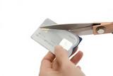 Debt concept - cutting a credit card poster