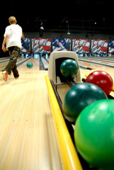 A bowling alley with balls in the rack