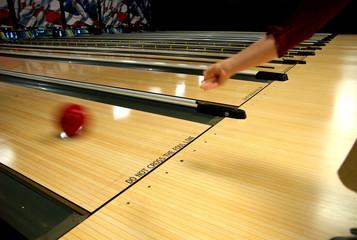 a human hand bowling a ball down a lane.