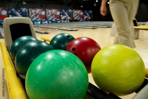 Bowling balls in the rack at a bowling alley.