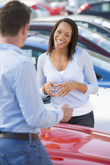 Young woman talking to car salesman