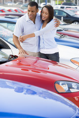 Young couple looking at new cars