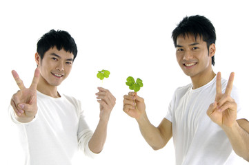 Young man holding up a green leaf by posing