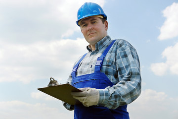 Construction site manager with notepad