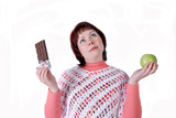 Young  woman choosing between an apple and chocolate poster