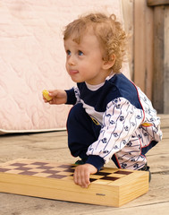 little curly boy holds a chess-board
