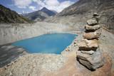 memorial stones piled , blue mountain lake, annapurna, nepal poster