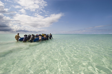 zanzibar diving tourists walking inflatable boat out of shallow