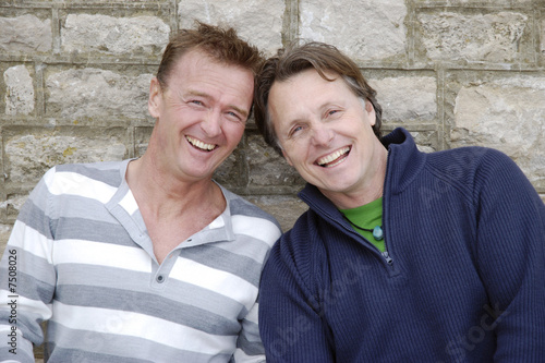 A happy gay couple laughing.