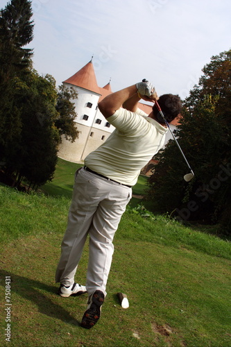 Golfer strikeing a ball.