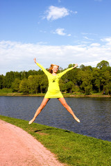 The happy girl jumps on the bank of the river
