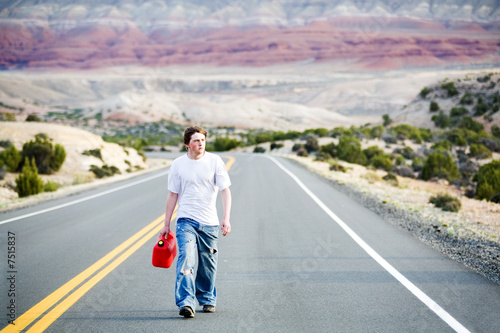teenager out of gas walking down road with empty can
