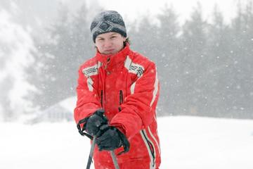 young man by mountain skies at snowfall