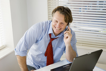 A happy smiling businessman on the phone.