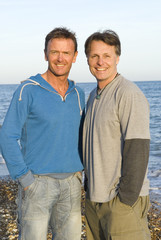 A happy gay couple at beach.