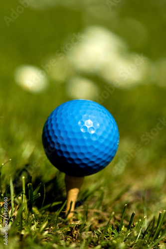 Blue golf ball on wooden tee Focus on ball Portrait orientation.