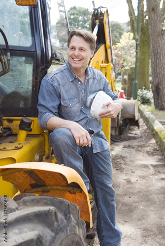 A happy smiling builder sitting on his digger.