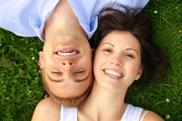 young and happy couple smiling on a meadow