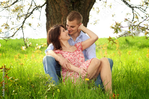young and happy couple is cuddle on a meadow