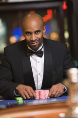 Man gambling in casino at roulette table