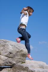 Kind springt von einem Stein