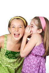 Two young gradeschool girls telling secrets and laughing