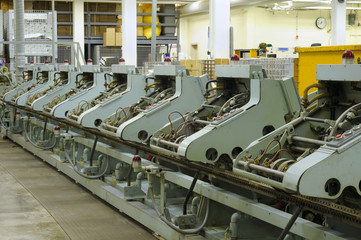 Row of stitching machines for binding booklets in publishing