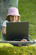 Cute little girl with laptop in the garden.