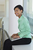 Business woman using laptop sitting on window ledge, side view