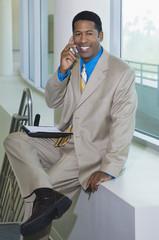 Business man using mobile phone sitting on window ledge, portrait