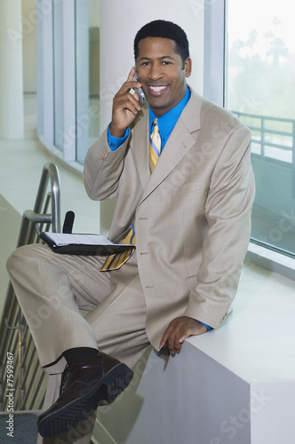 Business man using mobile phone sitting on window ledge, portrait
