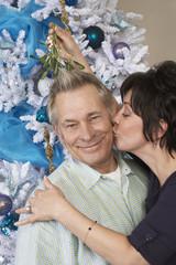 Senior woman kissing man under mistletoe