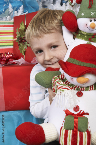 Boy 5-6 holding stuffed snowman in front of Christmas tree, portrait