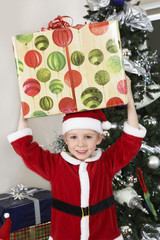Boy 5-6 in Santa costume holding present over head