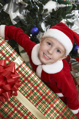 Boy 5-6 in Santa costume holding present by Christmas tree