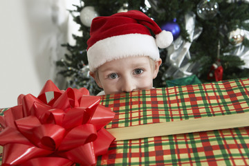Boy 5-6 in Santa costume peeking over present by Christmas tree